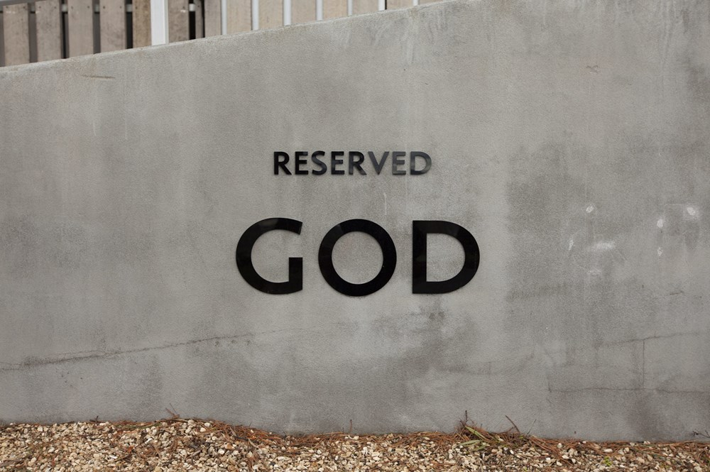 Parking space with sign reading 'RESERVED, GOD'